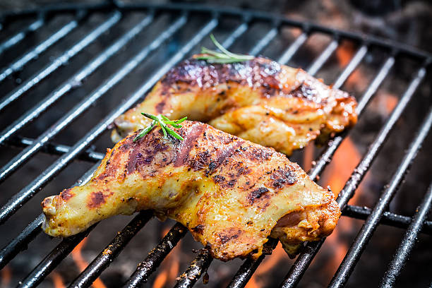 Roasted chicken legs on the grill with fire stock photo