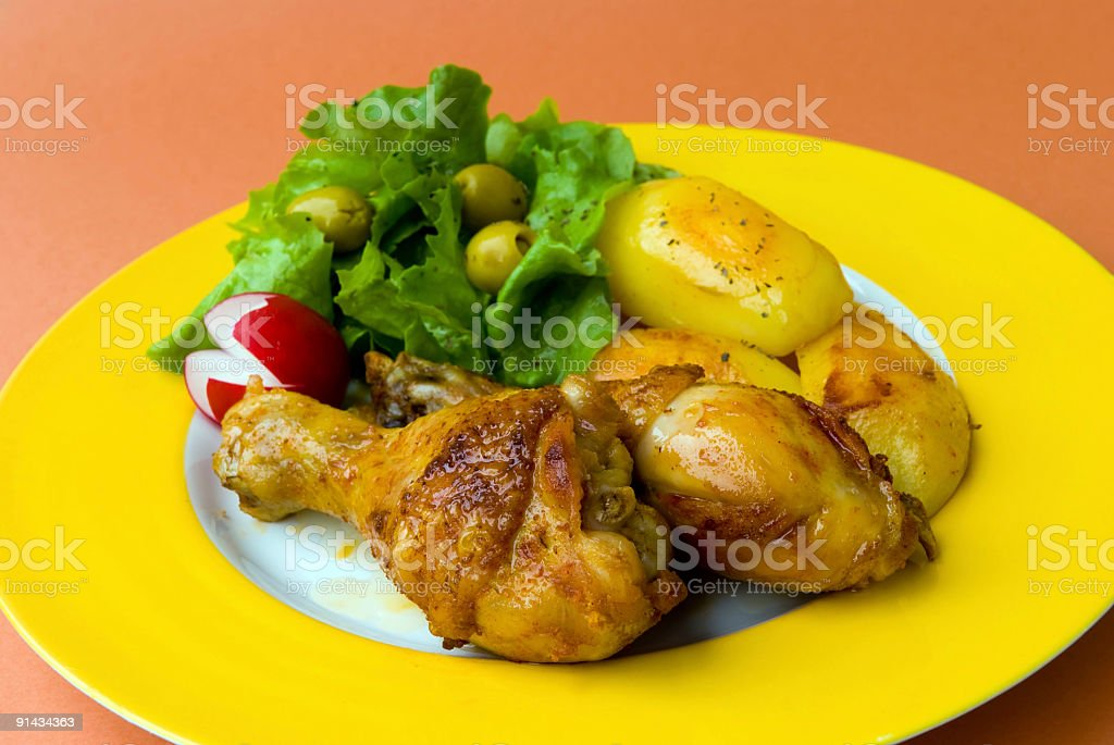 roasted chicken legs with fried potatoes and salad royalty-free stock photo