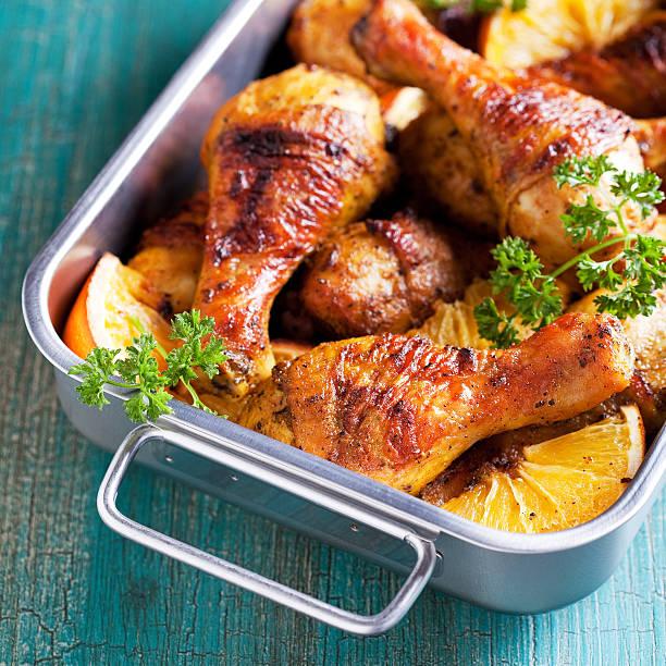 gebratenes hühnerfleisch beine mit orange - hühnerkeulen stock-fotos und bilder