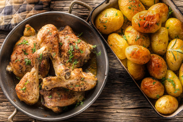 Roasted chicken legs with potatoes cumin pepper and herbs top of view Roasted chicken legs with potatoes cumin pepper and herbs top of view. drumstick stock pictures, royalty-free photos & images
