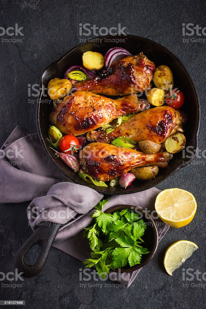 Roasted chicken legs with vegetables stock photo