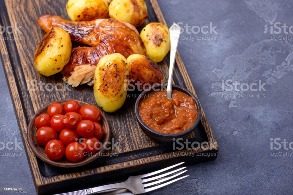 Roasted chicken meat and potato with sauce stock photo