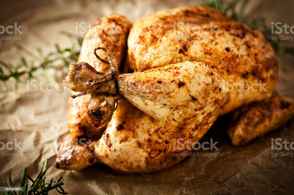Roasted chicken on brown wrapping paper stock photo