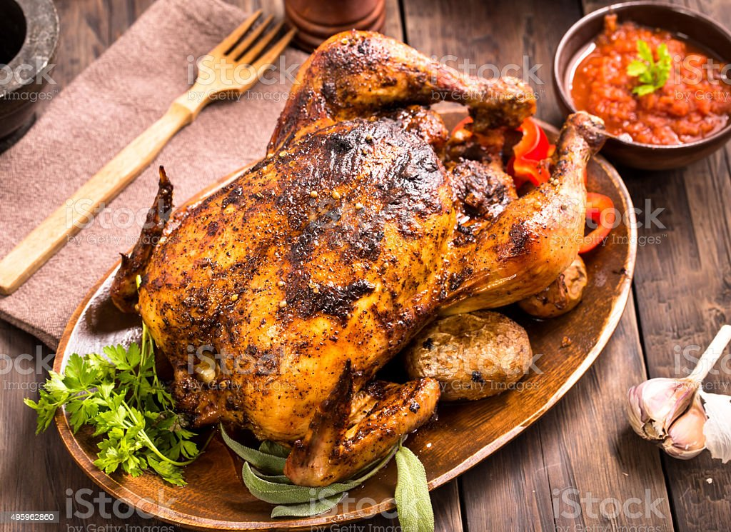 Roasted chicken on wooden plate stock photo