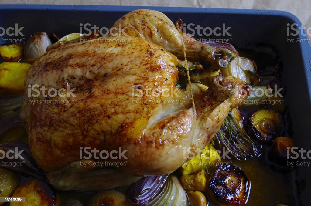 Roasted chicken, onions, and carrots in a pan stock photo