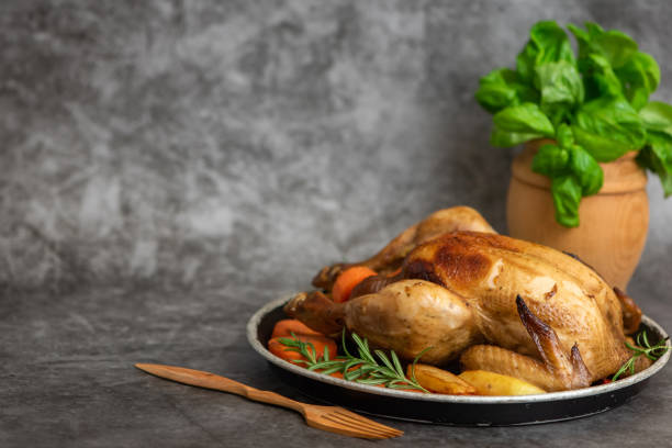 roasted chicken, potatoes and vegetables in plate on grey background. side view. with copy space - girarrosto foto e immagini stock