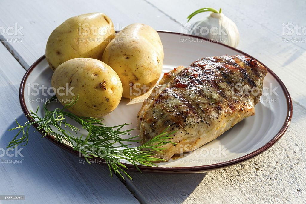 Roasted chicken served with potatoes and dill royalty-free stock photo