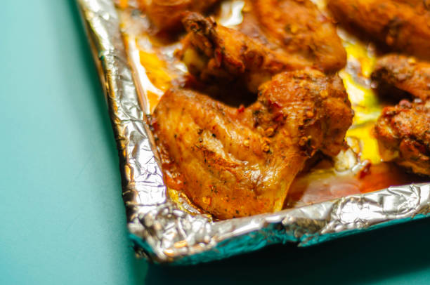Asas de frango assadas marinadas em um molho peri-peri picante - foto de acervo