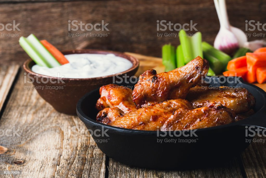 Roasted chicken wings with carrots, celery sticks and dipping sauce stock photo