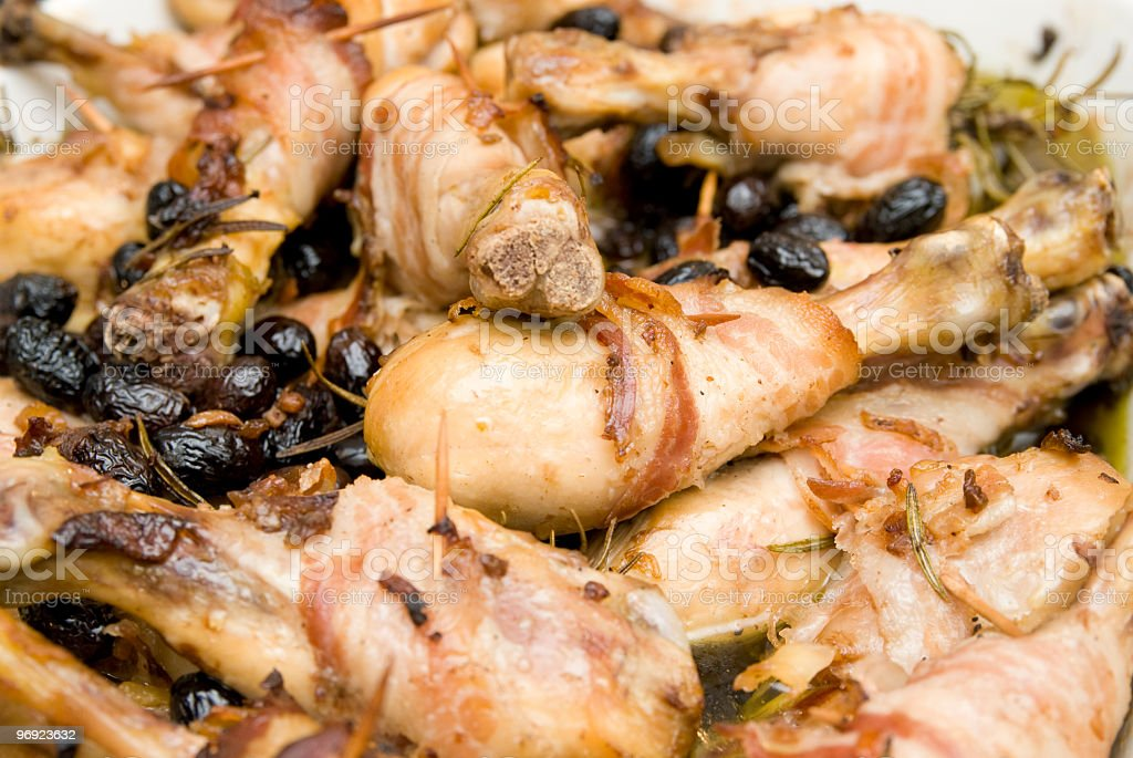 Roasted chicken with black olives cooked in the fire royalty-free stock photo