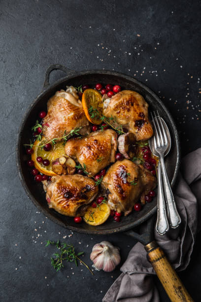 roasted  chicken with orange, cranberry and spicy herbs on pan roasted  chicken with orange, cranberry and spicy herbs on pan , black concrete background, copy space, top view, thyme photos stock pictures, royalty-free photos & images