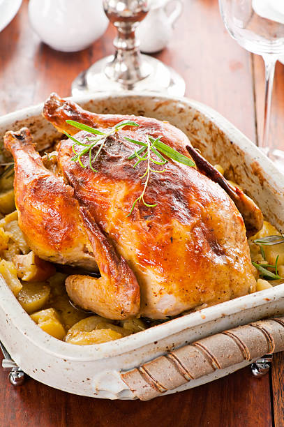 Roasted Chicken with Potato Roasted chicken with potato as closeup on a laid table cockerel stock pictures, royalty-free photos & images
