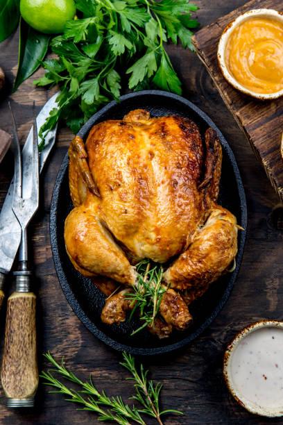 gebraden kip met rozemarijn geserveerd met sauzen op houten tafel, bovenaanzicht op de zwarte plaat. - geheel stockfoto's en -beelden