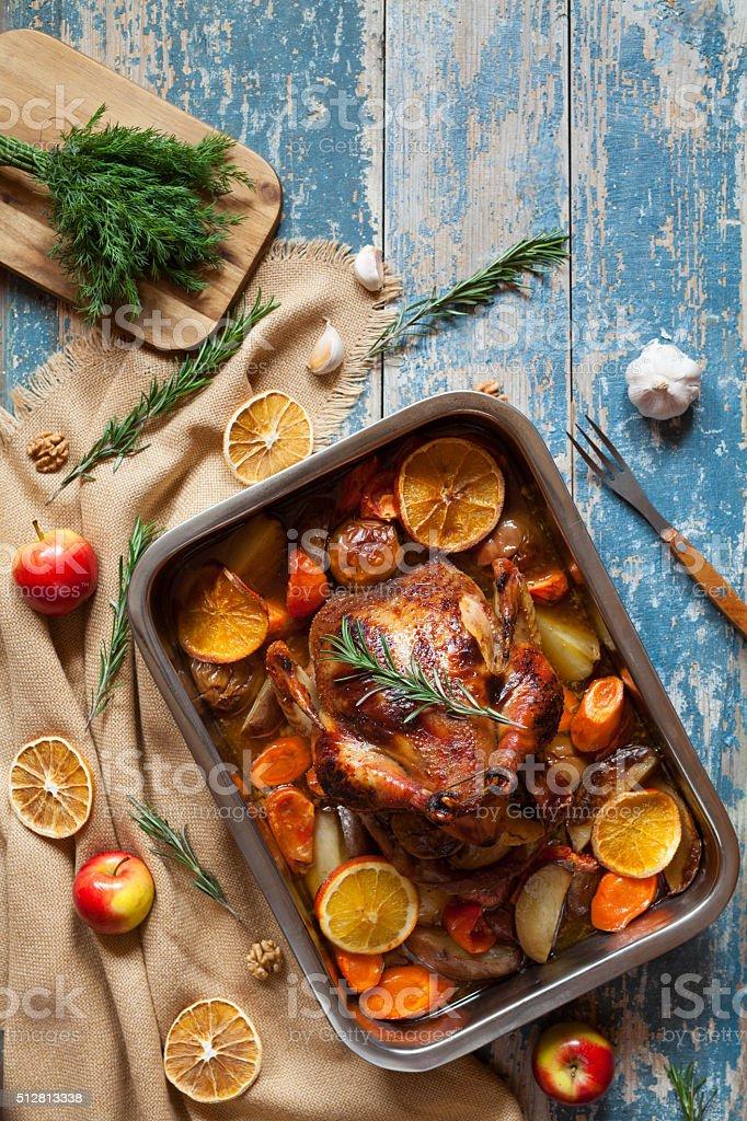 Gebratenes Huhn mit Gemüse und Kräutern auf Jahrgang Holztisch – Foto