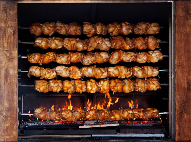 Roasted chickens on spit grilled over fire of a big barbecue Roasted chickens on spit grilled over fire of a big barbecue. spit roasted stock pictures, royalty-free photos & images
