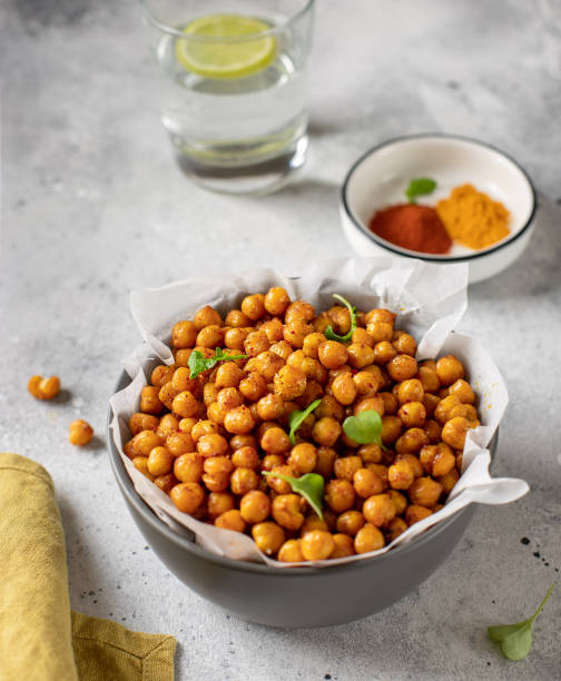 Roasted chickpeas with spices in bowl. healthy food concept. Roasted chickpeas with spices in bowl. healthy food concept. gray concrete background, vertical image chick pea stock pictures, royalty-free photos & images