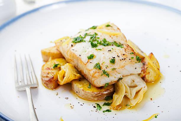 merluzzo arrostito, merluzzo bianco con patate al forno con sugo e carciofi - trout foto e immagini stock
