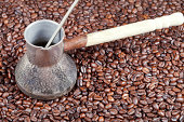 vintage coffee pot with spoon and many roasted coffee beans background