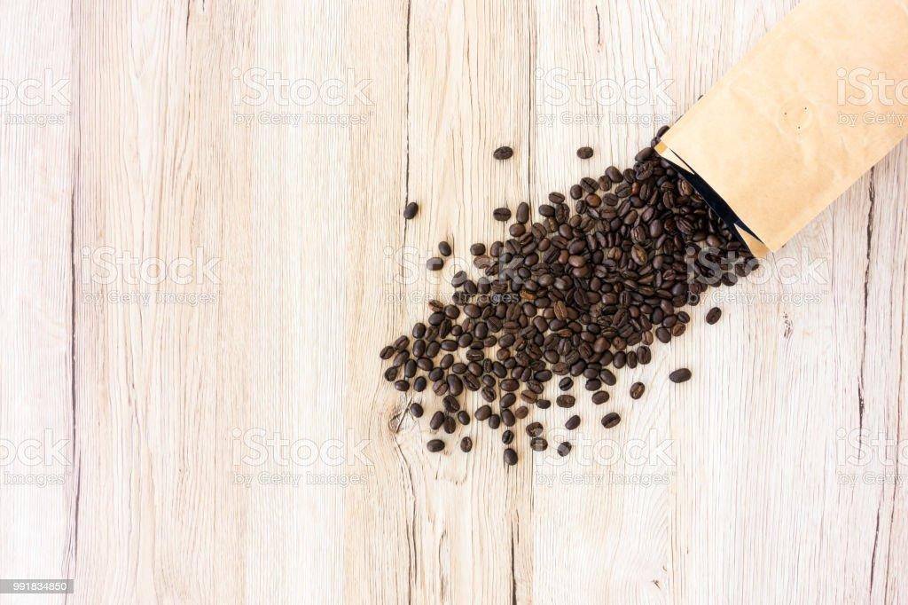 Geröstete Kaffeebohnen und Papiertüte mit Kaffeebohnen gefüllt – Foto