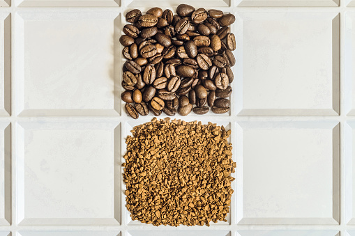istock Roasted coffee beans arabica and granules of freeze-dried instant coffee laid out in the form of a square on a white tray. Grocery background with copyspace. 824945694