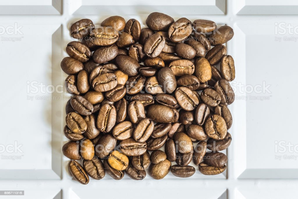 Roasted coffee beans arabica laid out square in a white tray stock photo