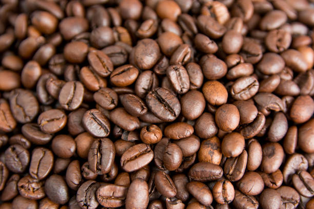 roasted coffee beans background, brown coffee beans for can be used as a background - coffee beans stock photos and pictures