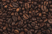 istock Roasted coffee beans. Background, close-up top view. Healthy breakfast. 1048277036
