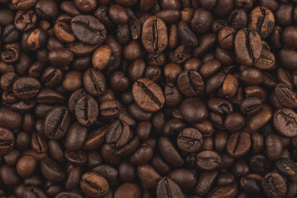 Roasted coffee beans. Background, close-up top view. Healthy breakfast. Fresh coffee grains wallpaper. Good morning. Coffee shop. caffeine stock pictures, royalty-free photos & images