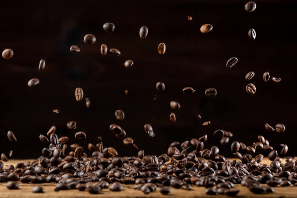 Roasted coffee beans falling down on wooden table stock photo