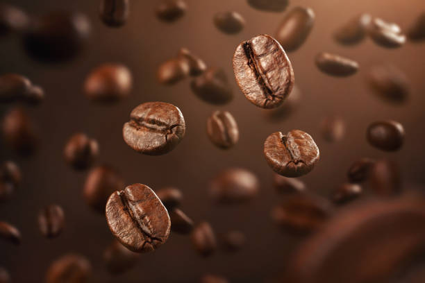 roasted coffee beans falling down - coffee stock pictures, royalty-free photos & images