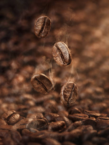 Roasted coffee beans falling down stock photo