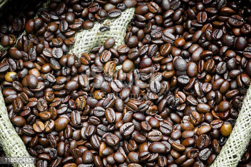 istock Roasted coffee beans falling in a burlap sack. Sackcloth bag with coffee beans, background. Coffee export. 1180724457