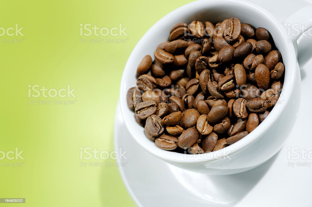 roasted coffee beans in cup against green royalty-free stock photo