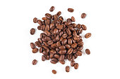 Heap of roasted coffee beans on white background