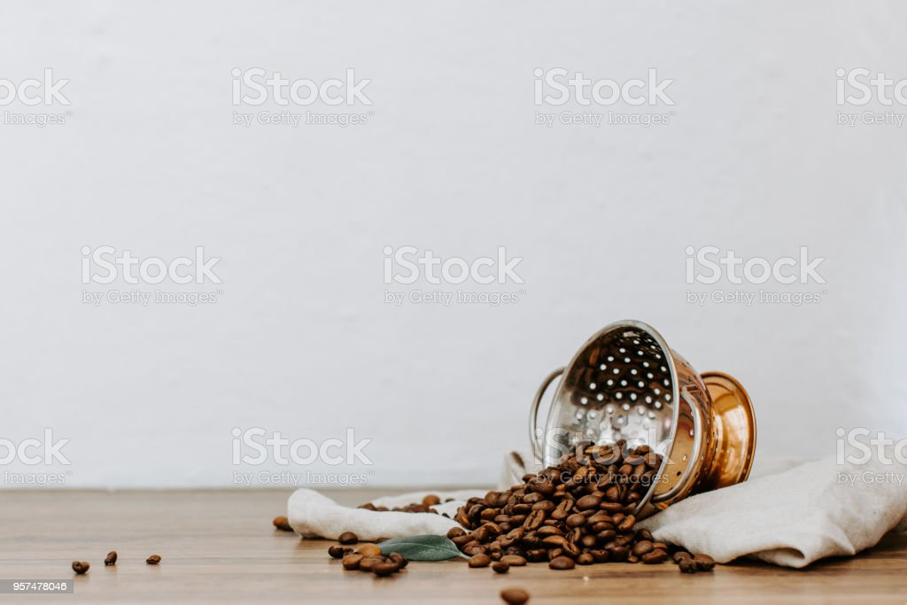 Roasted coffee beans on wooden table with linen napkin stock photo