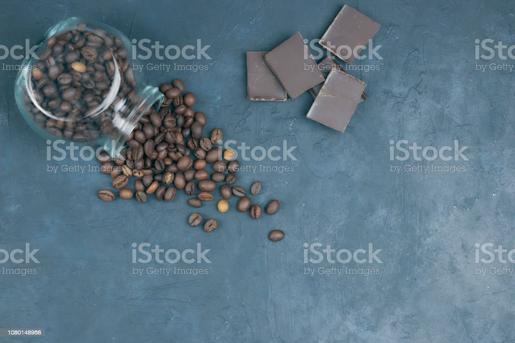 roasted coffee beans poured from a glass jar. angular placement of a coffee object with chocolate pieces. on dark concrete. view from above. copy space. stock photo