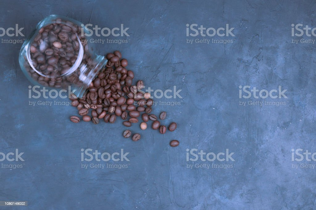 roasted coffee beans poured from a glass jar. angular placement of the coffee object. on dark concrete. view from above. copy space. stock photo