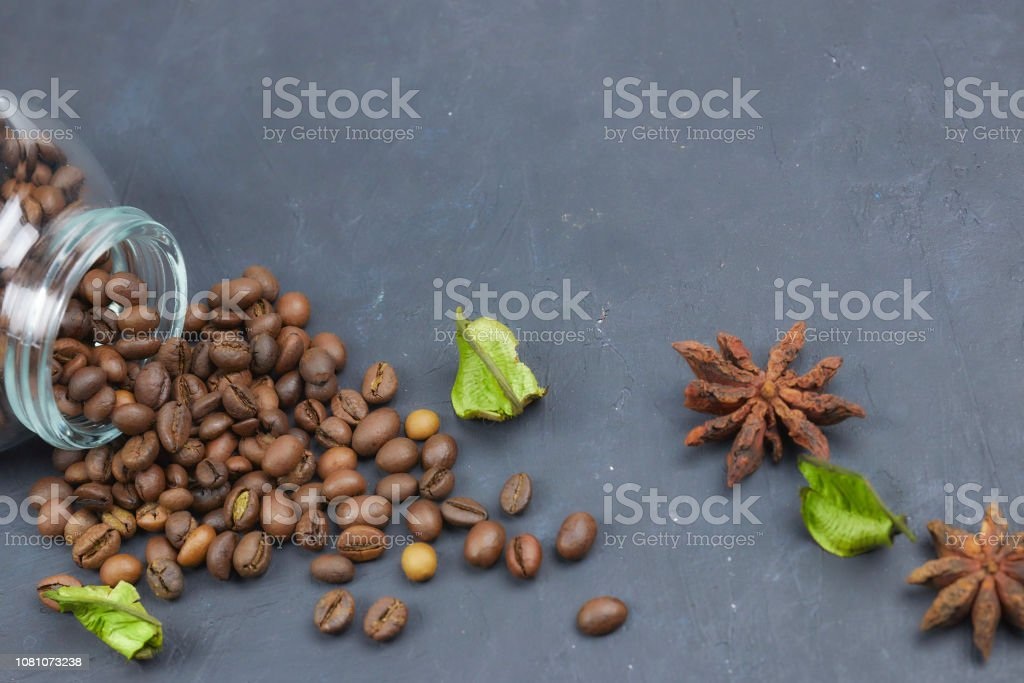 roasted coffee beans poured from a glass jar. angular placement of the coffee object. on dark concrete. horizontal view. copy space stock photo