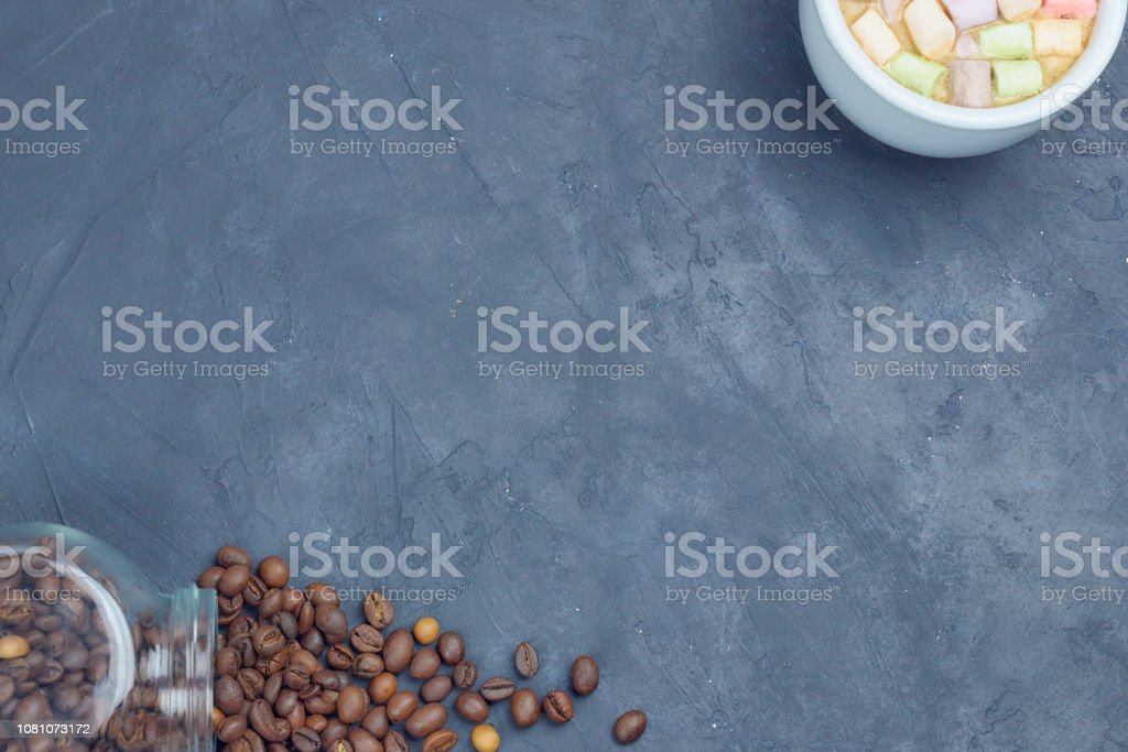 roasted coffee beans, poured from a glass jar with a white cup of coffee and marshmallow. angular placement of the coffee object. on dark concrete. view from above. copy space. stock photo