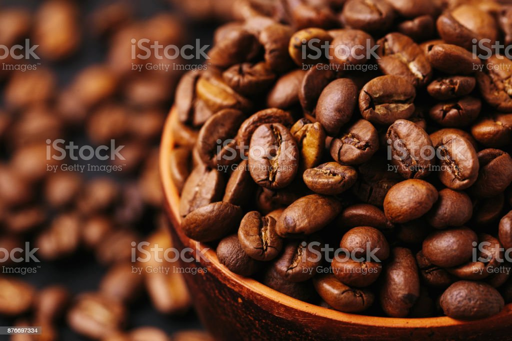 Roasted coffee beans scattered around. Gray background. Horizontal view stock photo