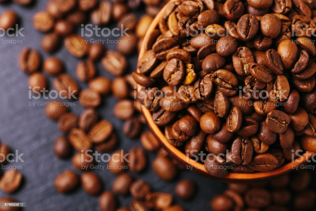 Roasted coffee beans scattered around. Gray background. Top view stock photo