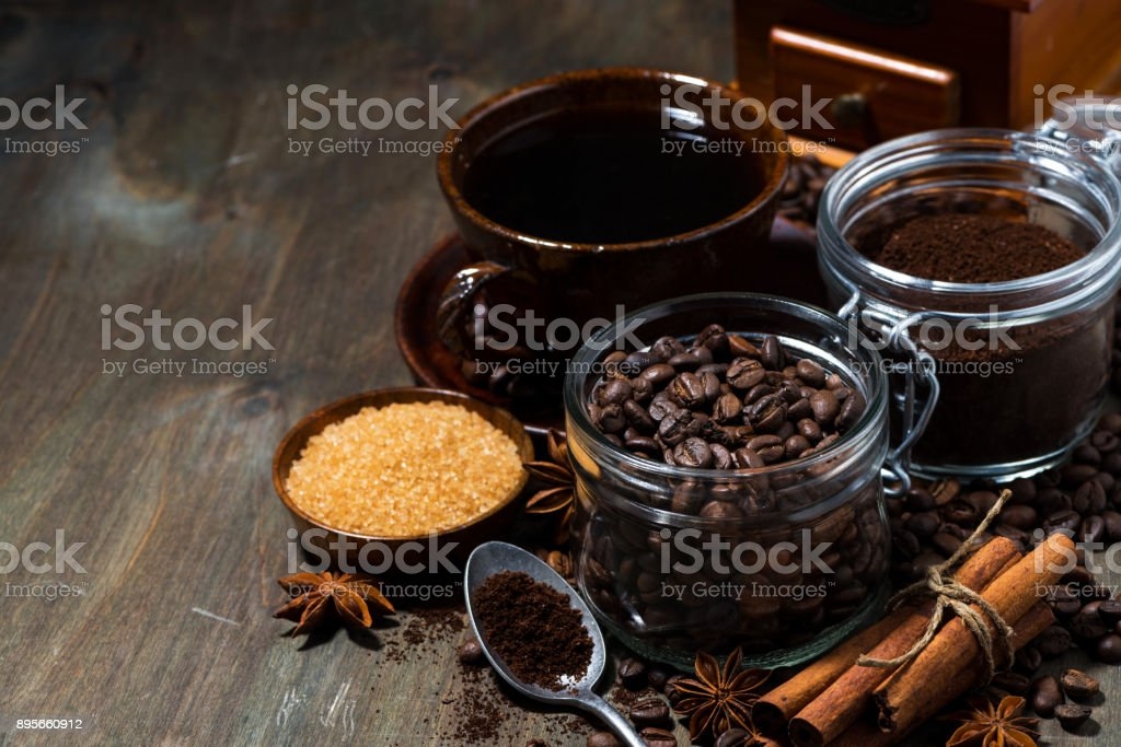 roasted coffee beans, spices and sugar on wooden background,...