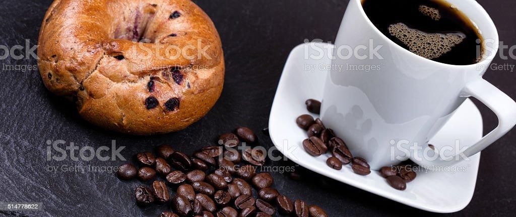 Grains de café torréfié avec une boisson et un bagel sur de l'ardoise - Photo