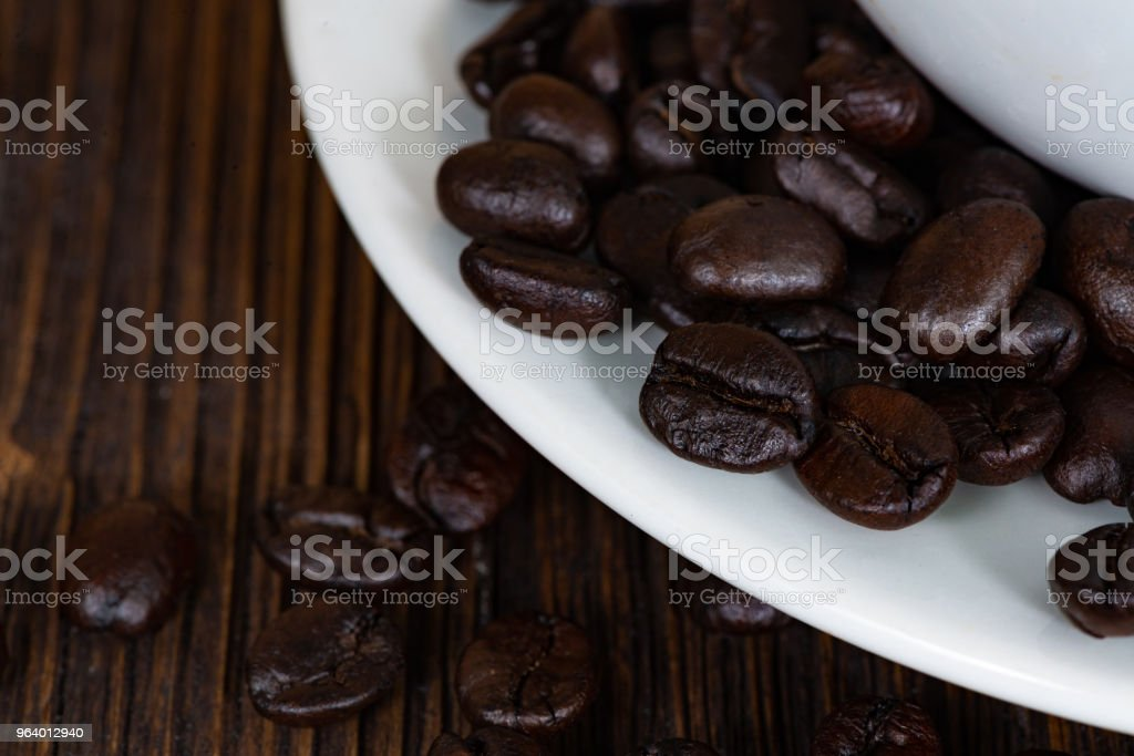 Roasted coffee beans with white cup on white wood table. coffee background with copy space.  Roasted coffee beans with white cup on dark brown wood table. coffee background with copy space for add text. - Royalty-free Backgrounds Stock Photo