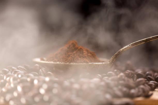 roasted coffee poured into an old silver spoon. - argento metallo caffettiera foto e immagini stock