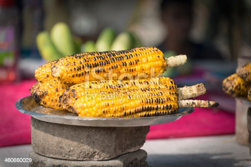 Hand roasted corn on the cob for sale by an outdoor street vendor in Mumbai (Bombay), India.