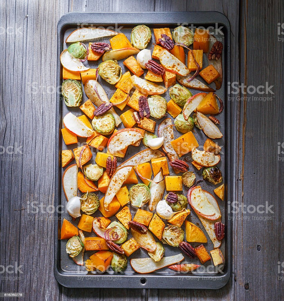 Roasted cut vegetables and fruit on a baking sheet. – Foto