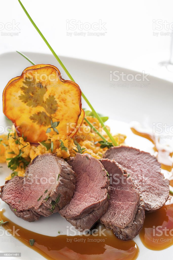 Roasted deer with smashed sweet potatoes and chips stock photo