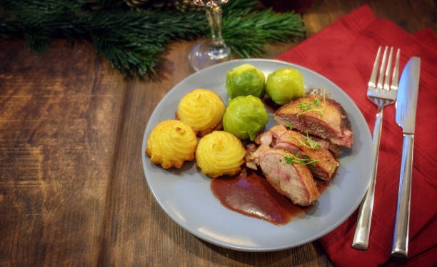 roasted duck breast with duchess potatoes, brussels sprout and sauce, served as a festive christmas dinner on a dark wooden table, copy space - duchessa foto e immagini stock