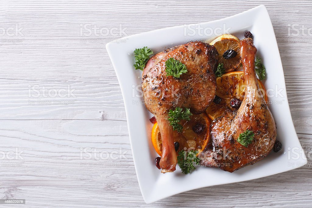 roasted duck leg with oranges and raisins top view, horizontal stock photo
